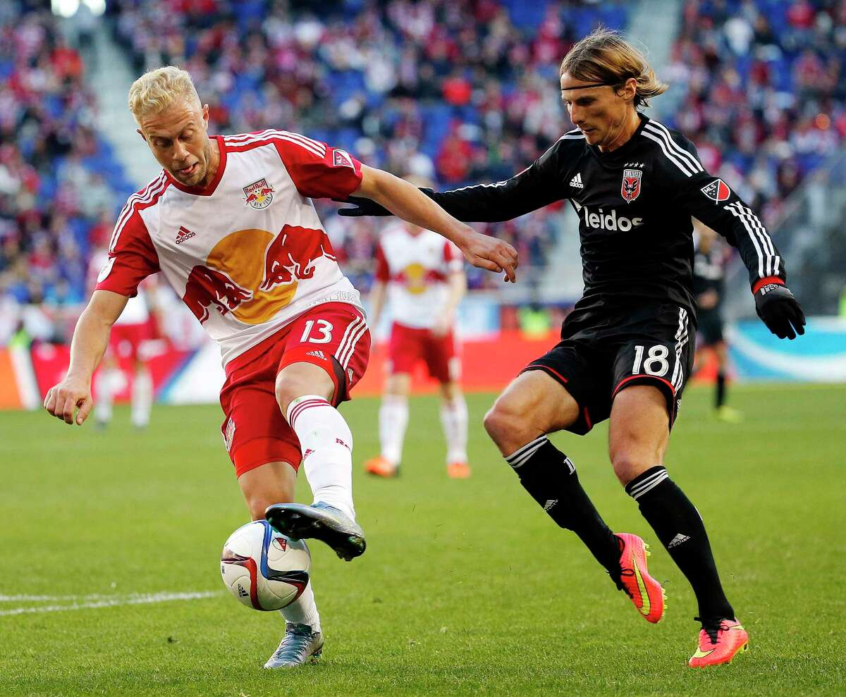 New York Red Bulls forward Mike Grella, left, dribbles against D.C. United forward Chris Rolfe during the first half Sunday.
