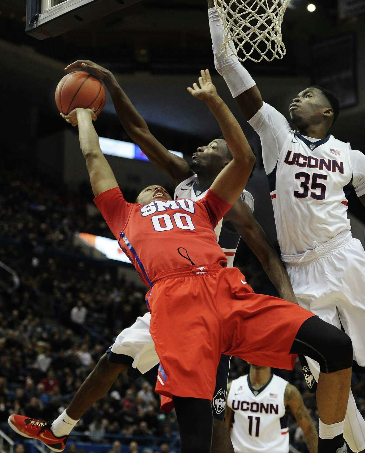 UConn's Daniel Hamilton, center, blocks a shot by SMU's Ben Moore as Amida Brimah helps out during a March 1 game in Hartford.