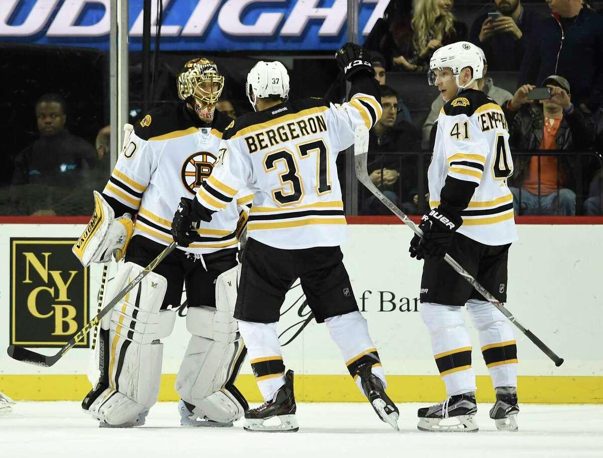 Bruins goalie Tuukka Rask (40), center Patrice Bergeron (37) and left wing Joonas Kemppainen (41) celebrate their 2-1 win over the Islanders on Sunday in New York.