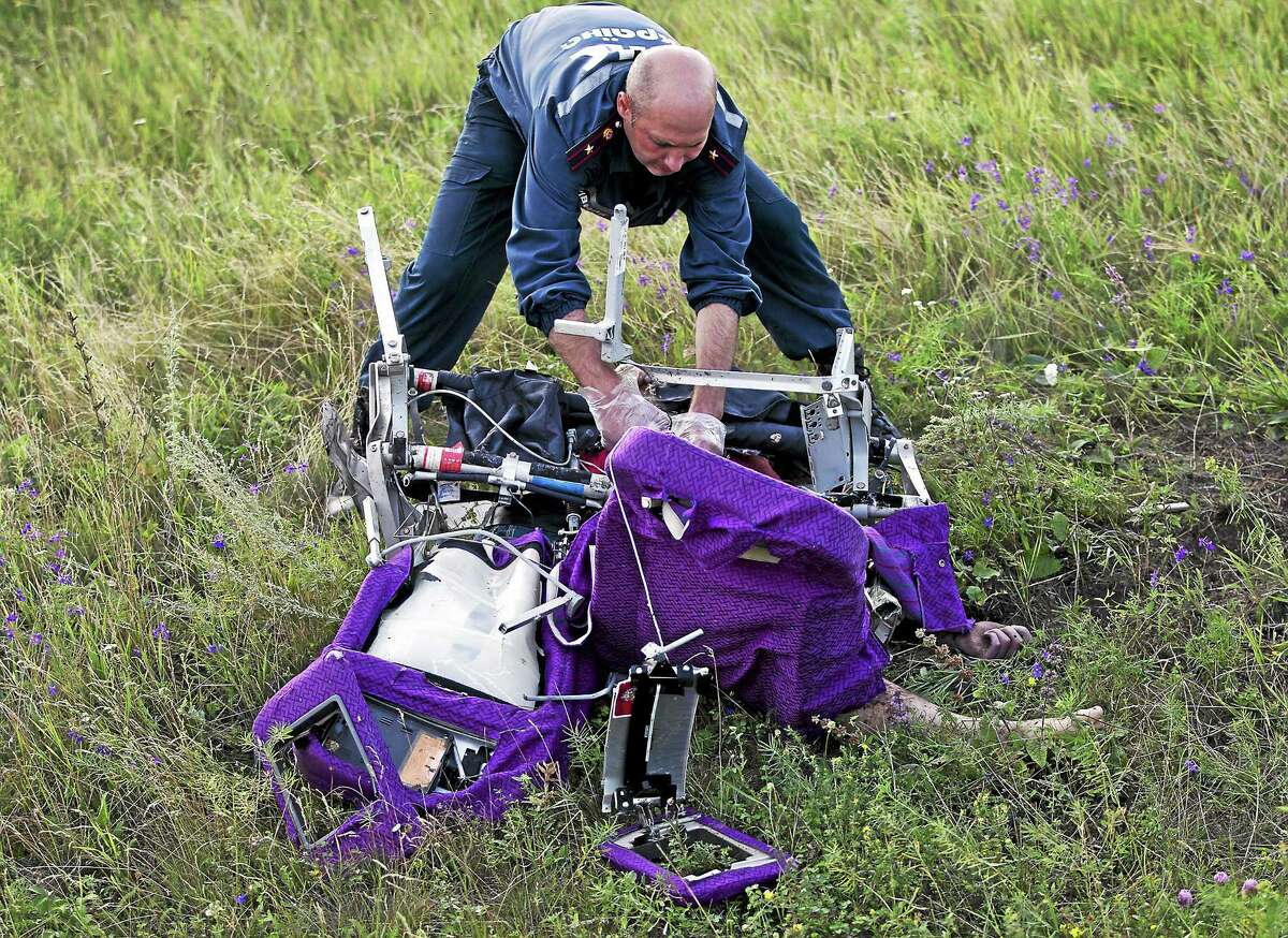 An emergency worker cuts through aircraft seat belts to free the body of a victim at the crash site of Malaysia Airlines Flight 17 near the village of Hrabove, eastern Ukraine on July 19, 2014.