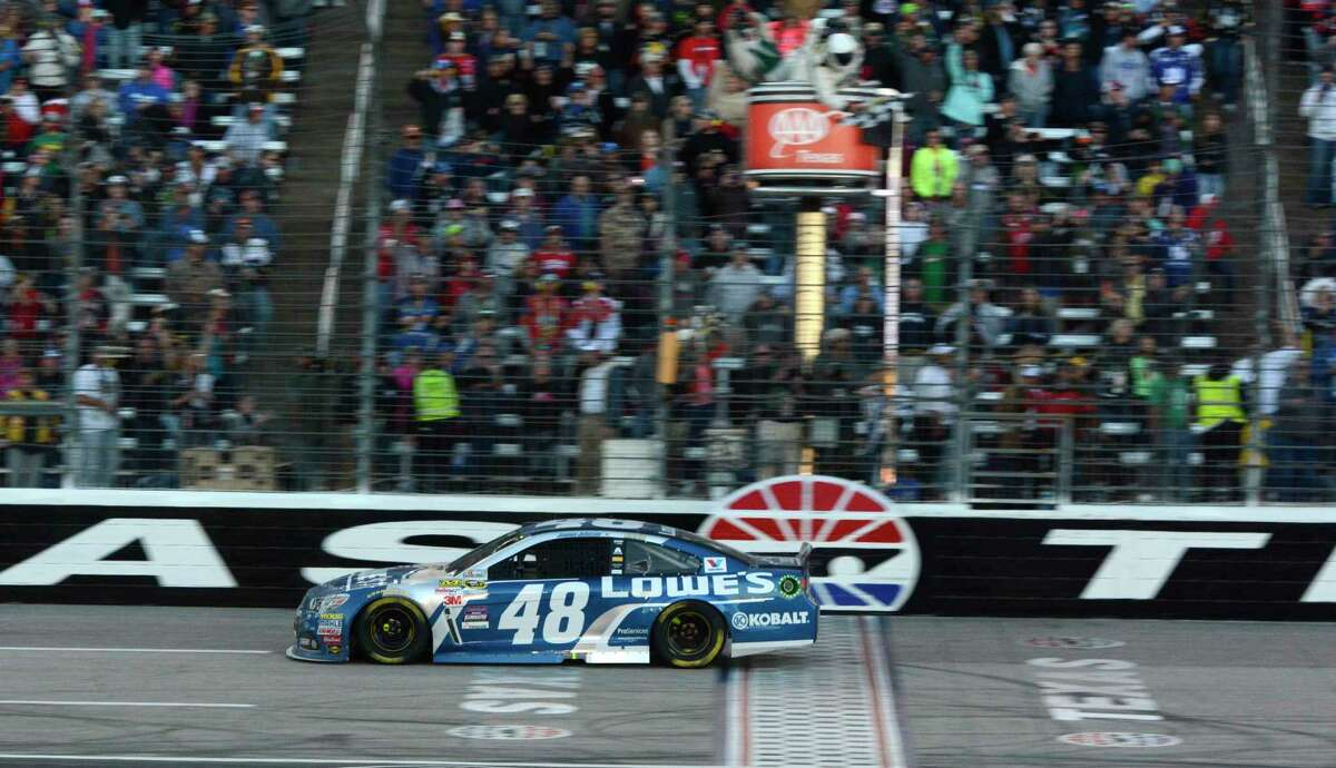 Jimmie Johnson (48) takes the checked flag while winning at Texas Motor Speedway on Sunday.