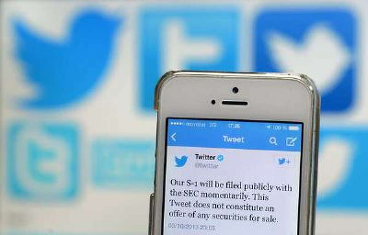 A Twitter tweet announcing the company's planned initial public offering (IPO) is pictured on a mobile telephone back-dropped by various twitter logos in Madrid on Oct. 4, 2013.