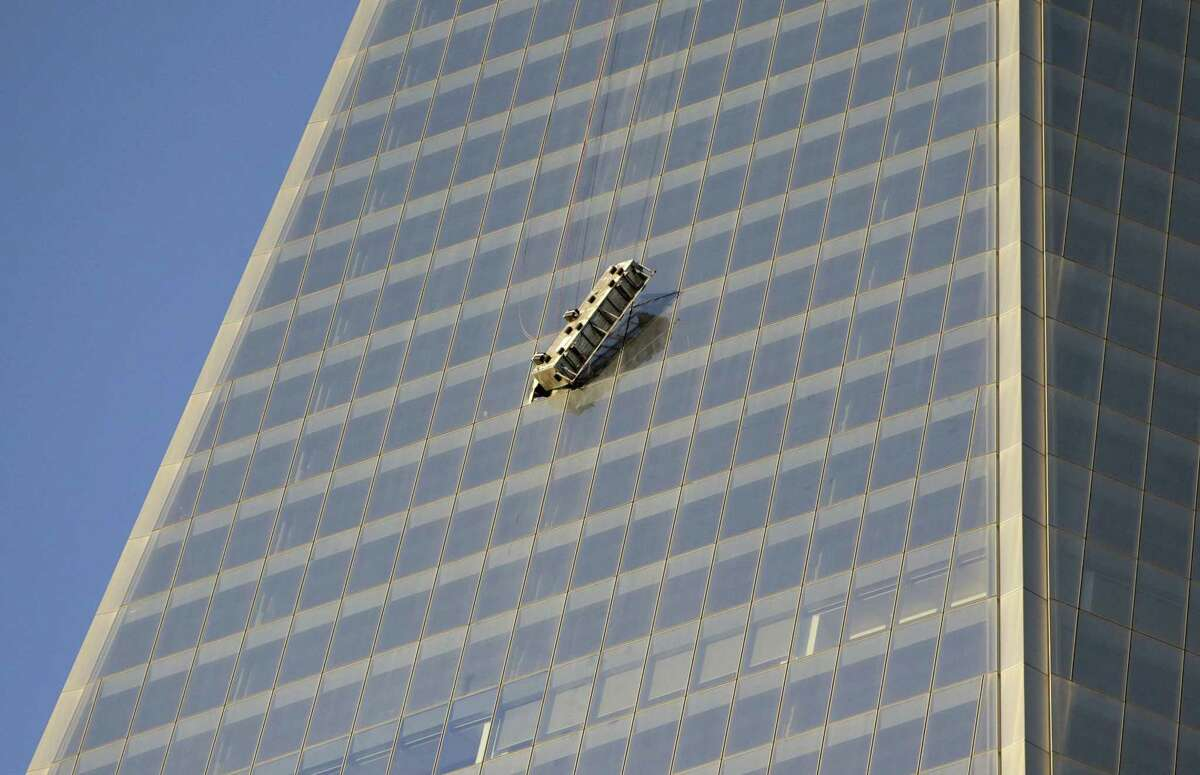 A scaffolding dangles precariously on the side of 1 World Trade Center hours after two window washers were rescued by firefighters who cut through a window to reach them, Wednesday, Nov. 12, 2014, in New York.