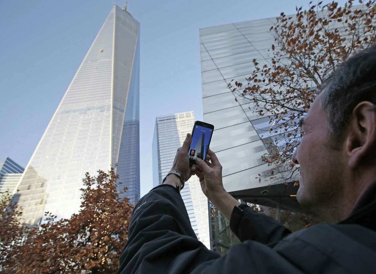 Tomas Vruns, from Muenster, Germany, uses his cell phone to take a picture of 1 World Trade Center where a scaffolding still dangled hours after two window washers were rescued by firefighters who sawed through a window to reach them, Wednesday, Nov. 12, 2014, in New York. The accident, which officials said was caused by a malfunctioning cable, happened little more than a week after workers began moving into the nation's tallest building.