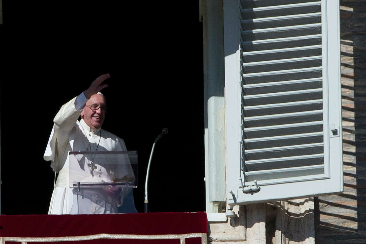 """Pope Francis delivers his blessing during his Angelus prayer from his studio window overlooking St. Peter's Square, at the Vatican on Nov. 8, 2015. In his first public comments on the latest scandal rocking the Vatican, Pope Francis told followers on Sunday that the theft of Vatican documents describing financial malfeasance inside the Holy See was a """"crime"""" but pledged to continue reforms."""