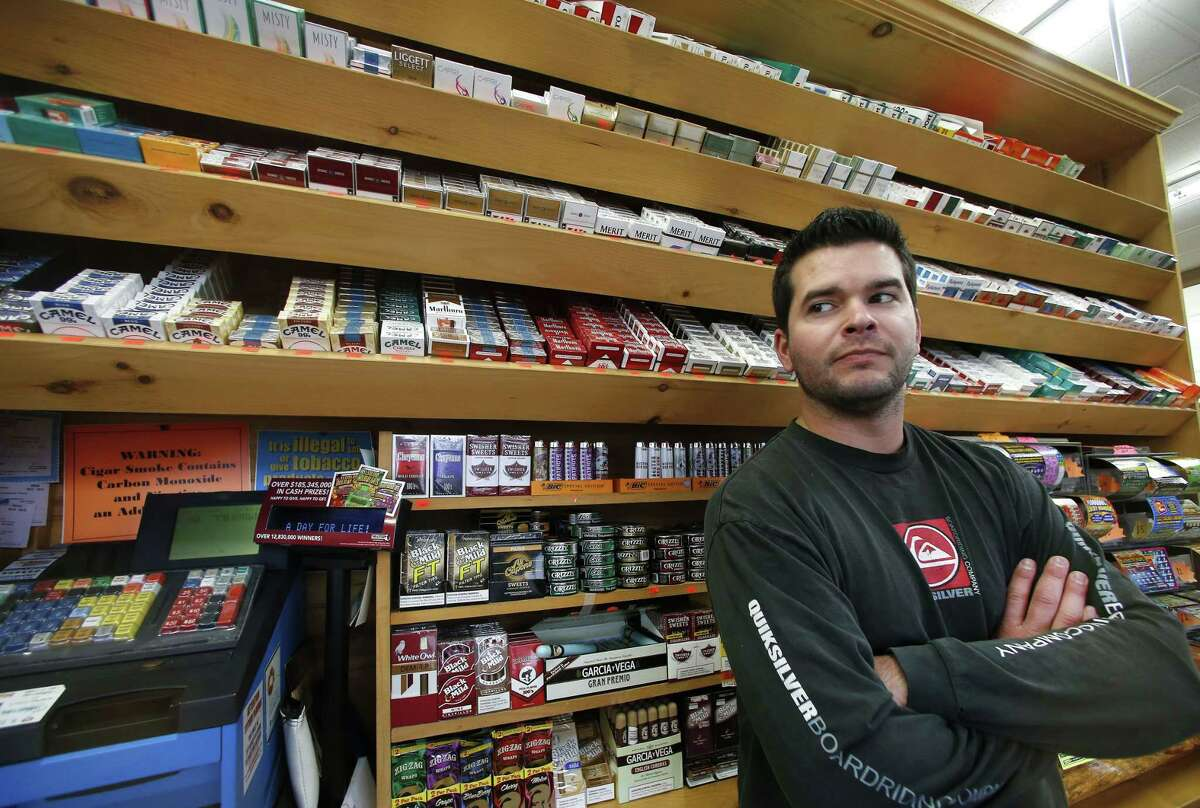 Brian Vincent poses in front of a large display of tobacco products at Vincent's Country Store in Westminster, Mass., Thursday, Nov. 6, 2014.