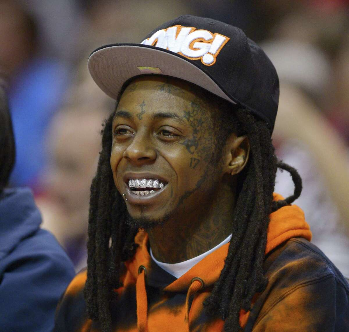 In this 2014 file photo, singer Lil Wayne watches the Los Angeles Clippers play the Houston Rockets during the first half of an NBA basketball game in Los Angeles.