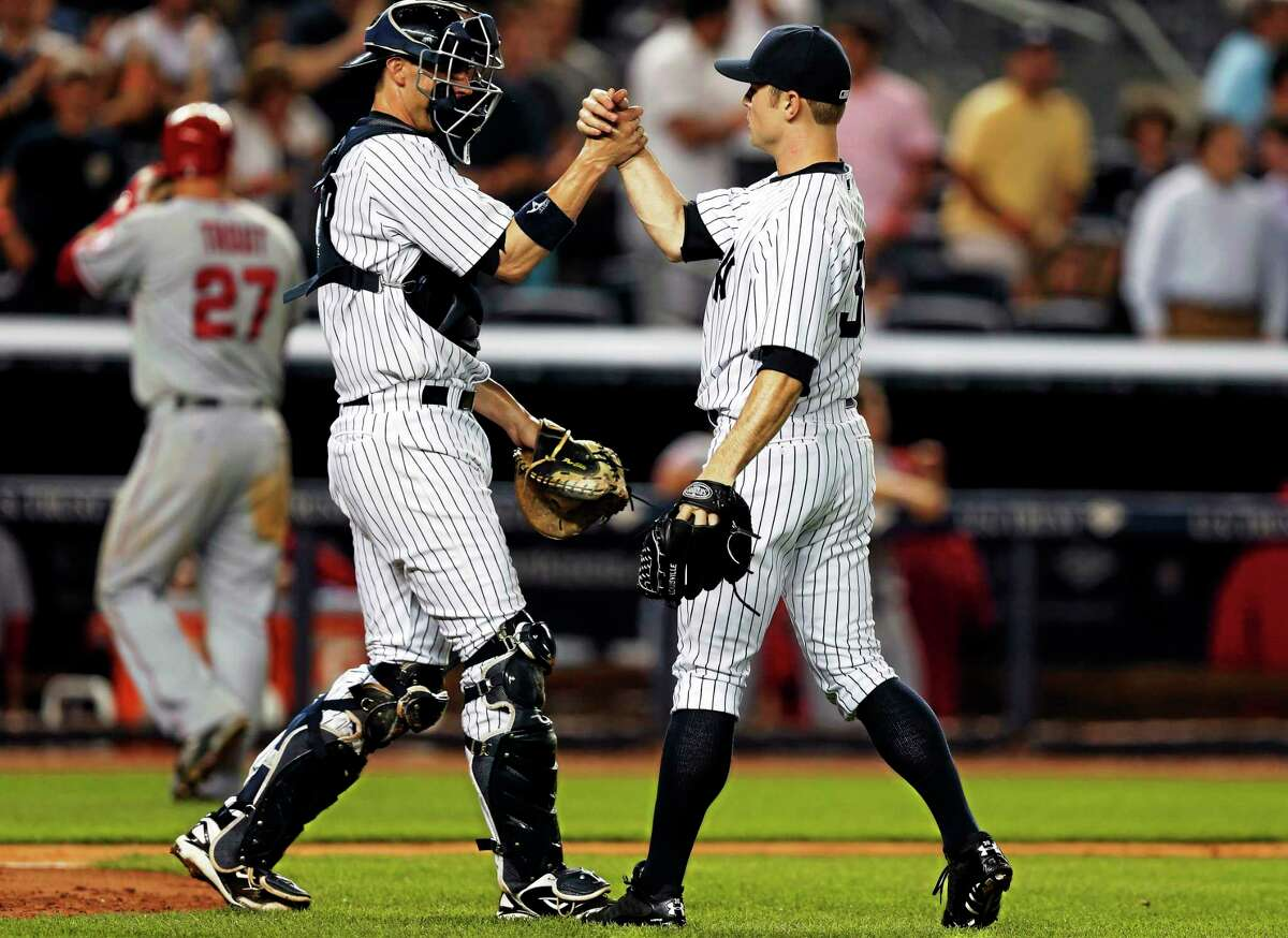The Los Angeles Angels' Mike Trout heads to the dugout as New York Yankees catcher Chris Stewart (19) congratulates reliever David Robertson on his save after the Yankees' 2-1 victory on Aug. 12, 2013, in New York.