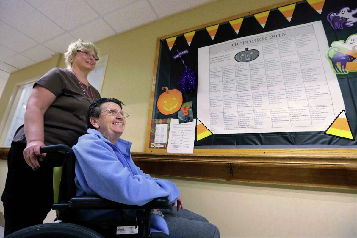 In this Oct. 22, 2015 photo, Burgess Square Health Center resident Jane Hail, 73, and center wellness director Rebecca Vrba talk next to the events calendar the two create together each month at the center in Westmont, Ill. Including Hail in the planning and scheduling of special events is part of the facility's efforts to provide person-centered care for residents.