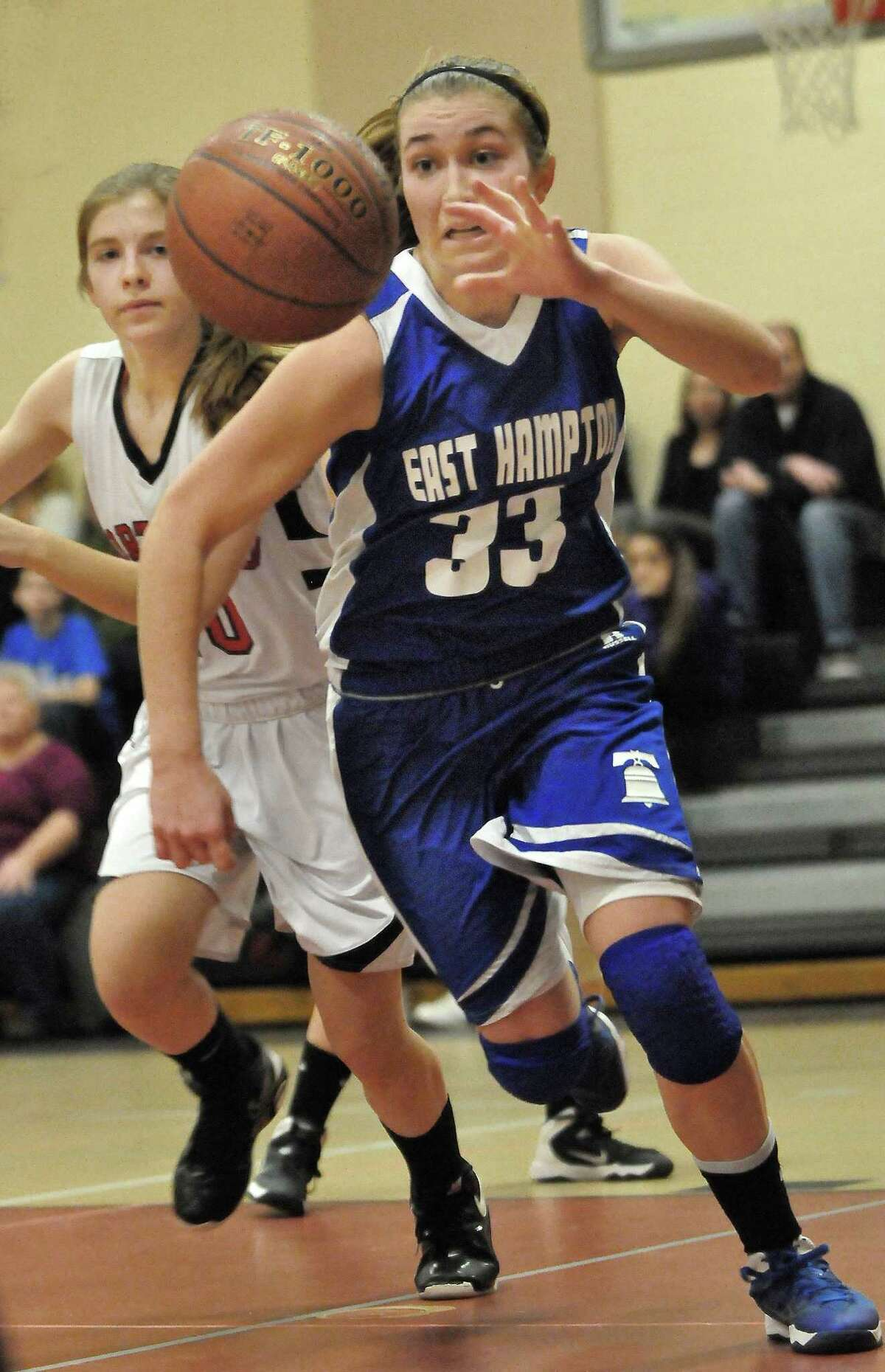 Catherine Avalone - The Middletown Press East Hampton sophomore Meghan Orbann grabs a rebound and drives the baseline past Portland's Courtney Cote Tuesday evening in Portland. The East Hampton Bellringers defeated the Portland Panthers 43 - 34.