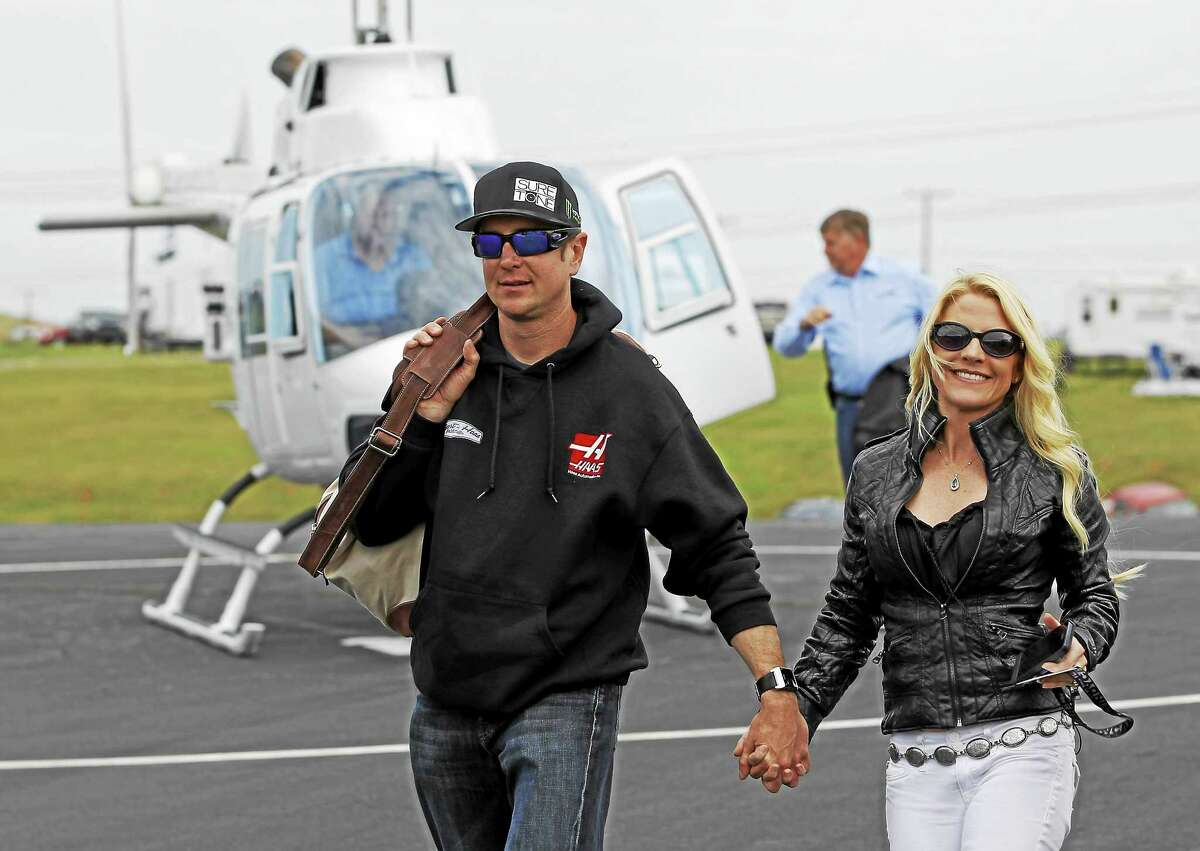 In this May 17, 2014 file photo, Kurt Busch, left, walks with his girlfriend, Patricia Driscoll, after arriving for the NASCAR Sprint All-Star race at Charlotte Motor Speedway in Concord, N.C.