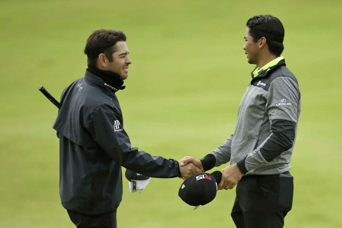 Jason Day, right, shakes hands with Louis Oosthuizen on the 18th green following their first round at the British Open on Thursday at the Old Course, St. Andrews, Scotland.