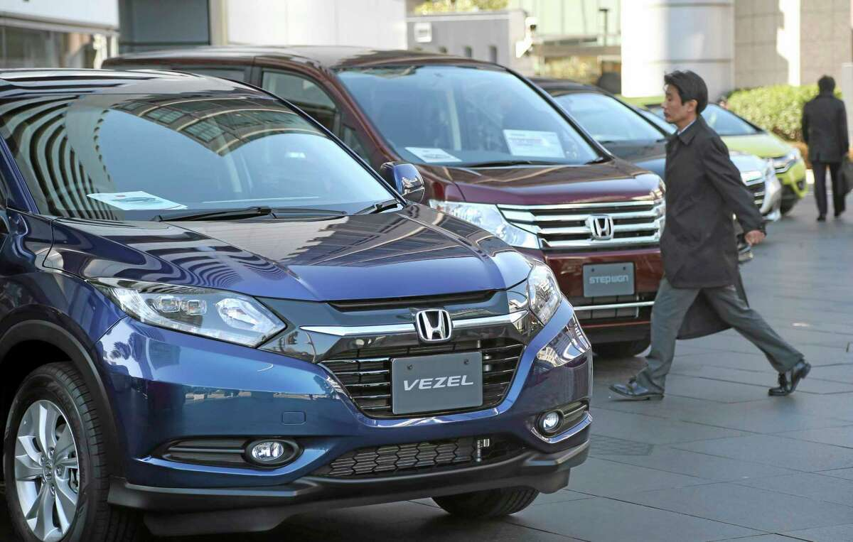A man walks past the headquarters of Honda Motor Co. in Tokyo, Friday, Jan. 31, 2014. Honda's fiscal third quarter profit doubled from a year earlier as sales got a big perk from a weak yen. Honda Motor Co. reported on Friday a 160.7 billion yen ($1.58 billion) net profit for the October-December quarter, up from 77.4 billion yen the year before.
