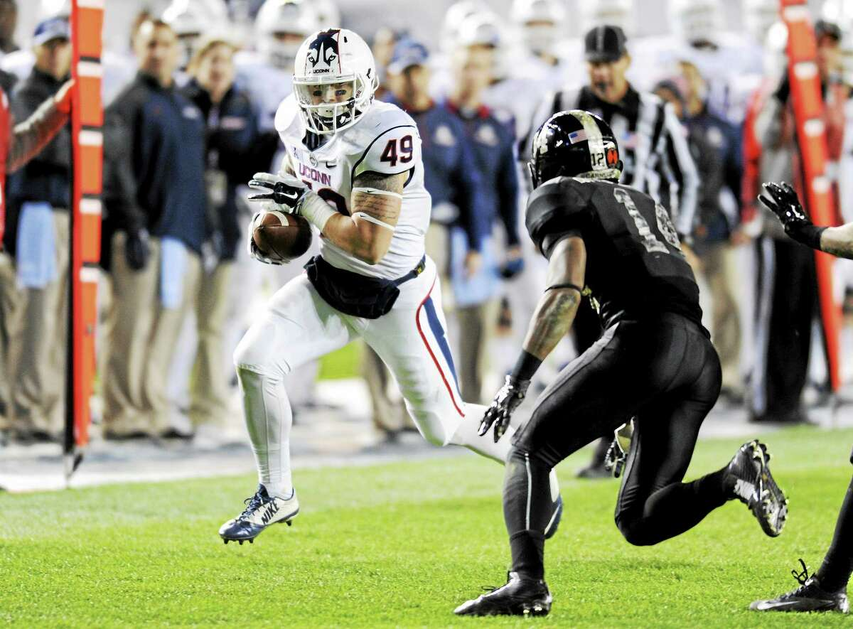 Then-Connecticut tight end Sean McQuillan, left, runs with the ball as Army defensive back Chris Carnegie closes in during the second half of an NCAA college football game on Nov. 8, 2014, at Yankee Stadium in New York. Army won 35-21.