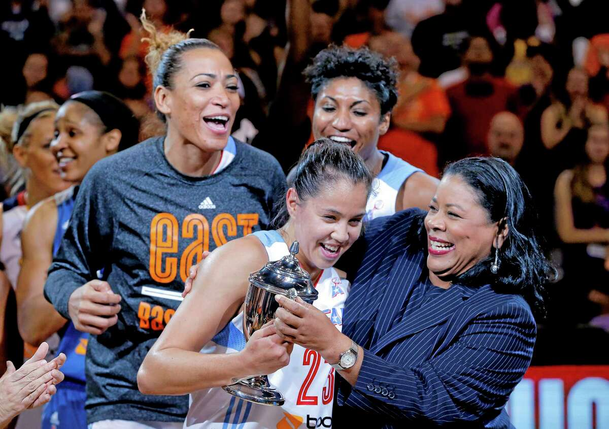 The East's Shoni Schimmel, of the Atlanta Dream, is presented the MVP trophy by WNBA President Laurel J. Richie, right, after the All-Star Game on Saturday in Phoenix. The East won 125-124 in overtime.
