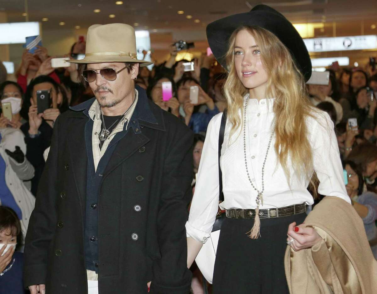 """FILE - In this Jan. 26, 2015 file photo, U.S. actor Johnny Depp and Amber Heard arrive at Haneda international airport in Tokyo to promote his latest film """"Mortdecai."""" Johnny Depp's wife Amber Heard has been charged with illegally bringing the couple's dogs to Australia. Prosecutors on Thursday, July 16, 2015 said that Heard was charged this week with two counts of illegally importing Pistol and Boo into Australia and one count of producing a false document. (AP Photo/Shizuo Kambayashi, File)"""