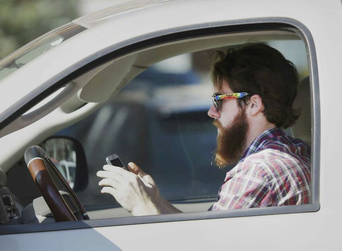 In this file photo, a man uses his cell phone as he drives through traffic. In a 2013 survey, 98 percent of motorists who own cellphones and text regularly were aware of the dangers, yet three-quarters of them admit to texting while driving, despite laws against it in some states.