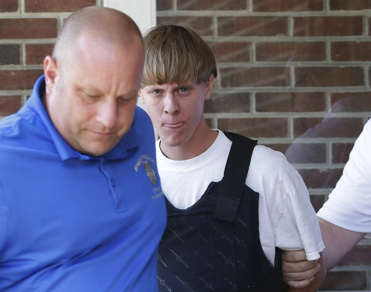 In this June 18, 2015 photo, Charleston, S.C., shooting suspect Dylann Storm Roof, center, is escorted from the Sheby Police Department in Shelby, N.C. He faces nine counts of murder, three counts of attempted murder and a weapons charge in the June 17 fatal shooting of nine black parishioners at Emanuel AME Church.