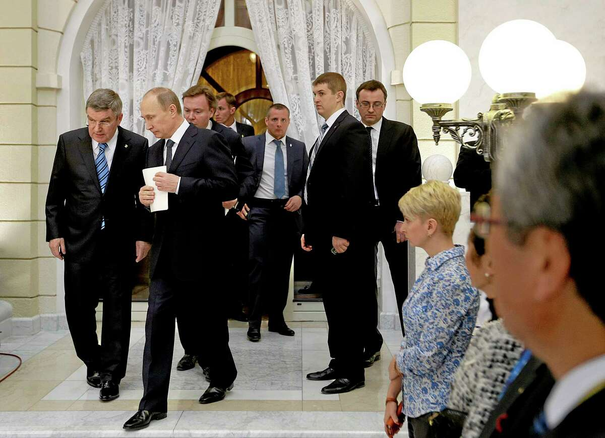 Russian President Vladimir Putin, second from left, and International Olympic Committee President Thomas Bach, left, step to the podium to speak at an event welcoming IOC members ahead of the upcoming 2014 Winter Olympics at the Rus Hotel, Tuesday, Feb. 4, 2014, in Sochi, Russia. (AP Photo/David Goldman, Pool)