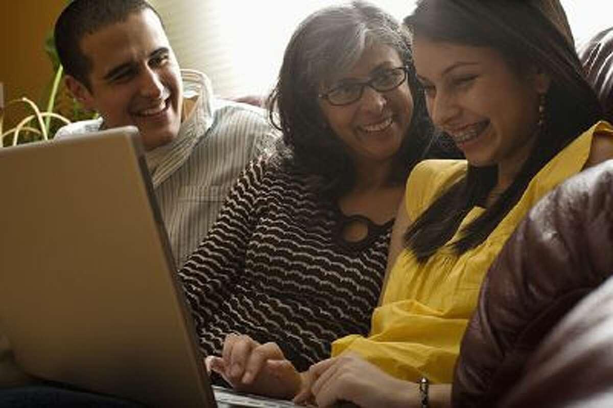 family laughing using laptop