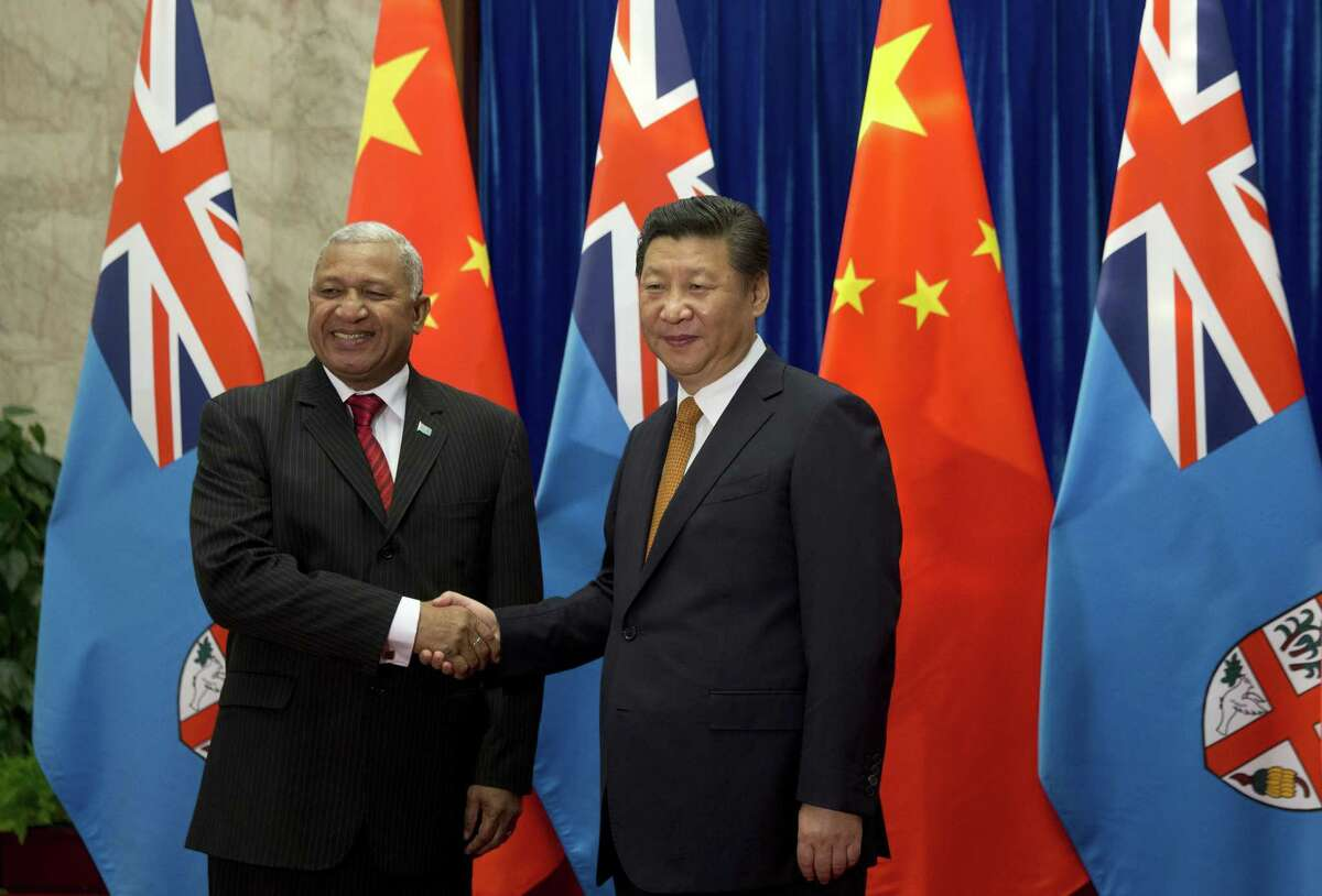 Fiji's Prime Minister Josaia Voreqe Bainimarama, left, shakes hand with Chinese President Xi Jinping before a meeting at the Great Hall of the People in Beijing Wednesday.