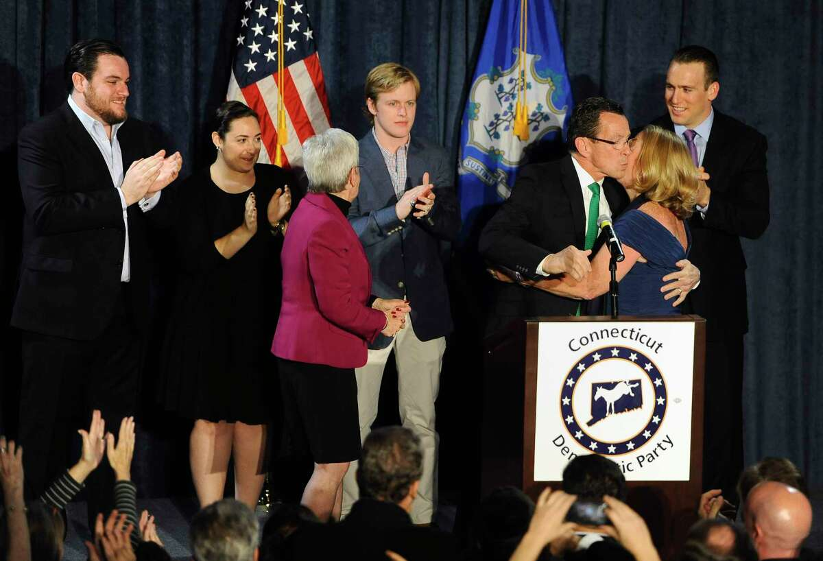 Incumbent Democratic Gov. Dannel P. Malloy kisses his wife Cathy Malloy after addressing supporters at his party's rally, Wednesday, Nov. 5, 2014, in Hartford, Conn.