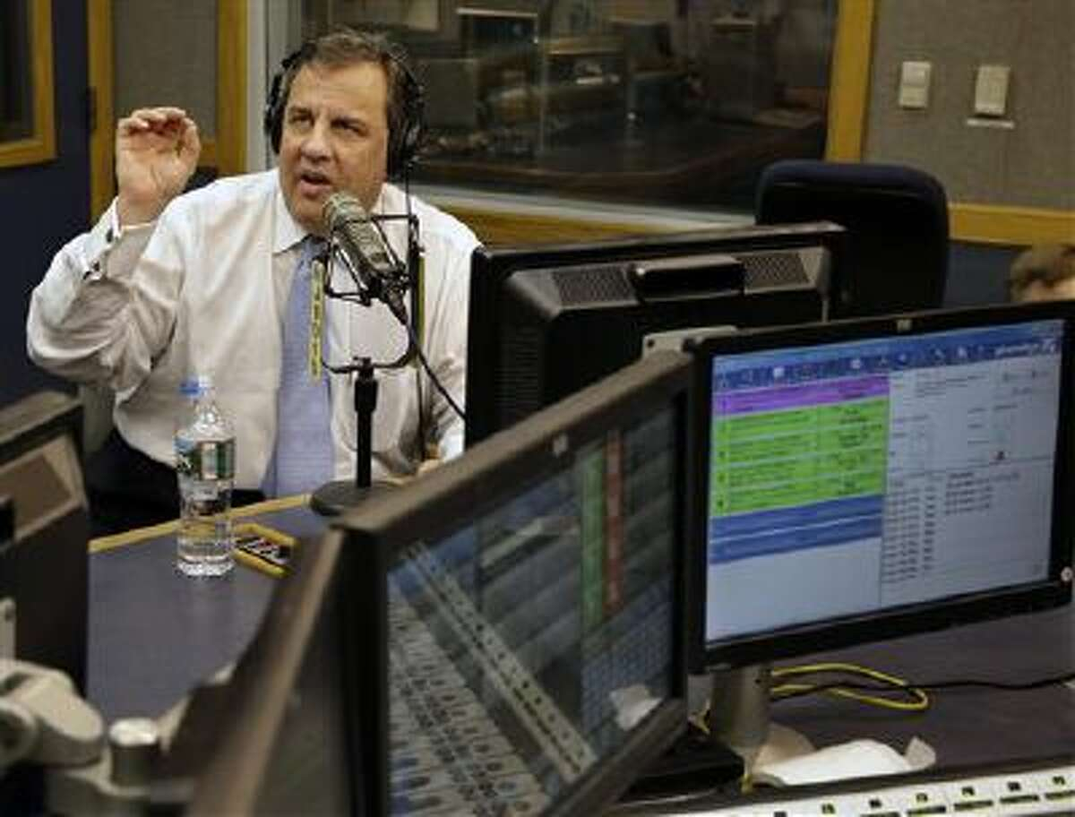 """New Jersey Gov. Chris Christie sits in a studio Monday during his radio program, """"Ask the Governor"""" broadcast in Ewing, N.J."""