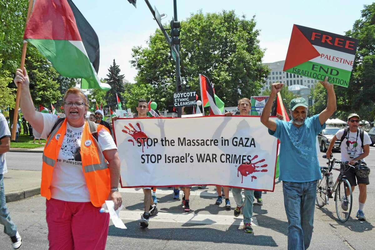 Demonstrators carry signs as they begin their march through downtown Denver, Colo., Saturday, to call for an end to what they called a humanitarian crisis brought on by conflict in Gaza.