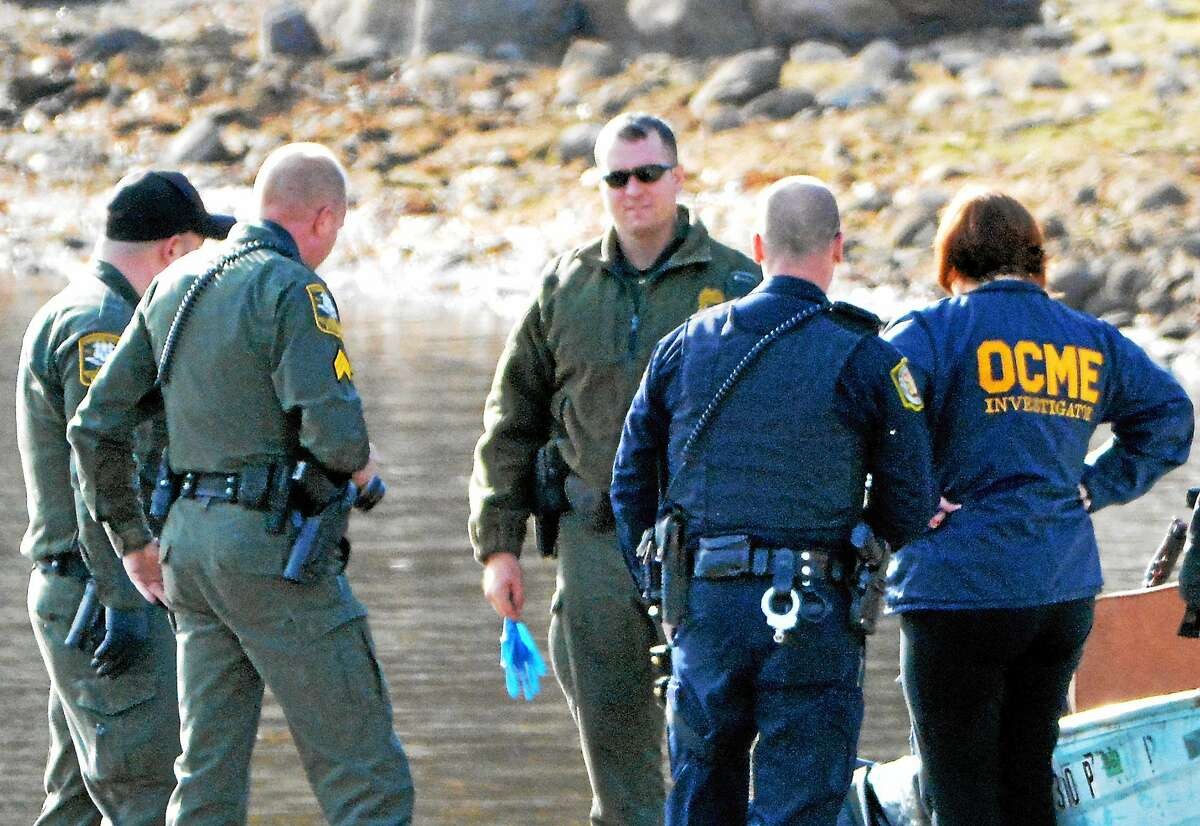 Officials from the state Office of the Chief Medical Examiner, state Environmental Conservation Police and the Winchester Police Department stand around the body of a man that was recovered from Winsted's Highland Lake Monday.