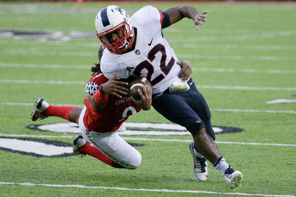 UConn running back Arkeel Newsome is tackled by Cincinnati cornerback Leviticus Payne during an Oct. 24 game in Cincinnati.