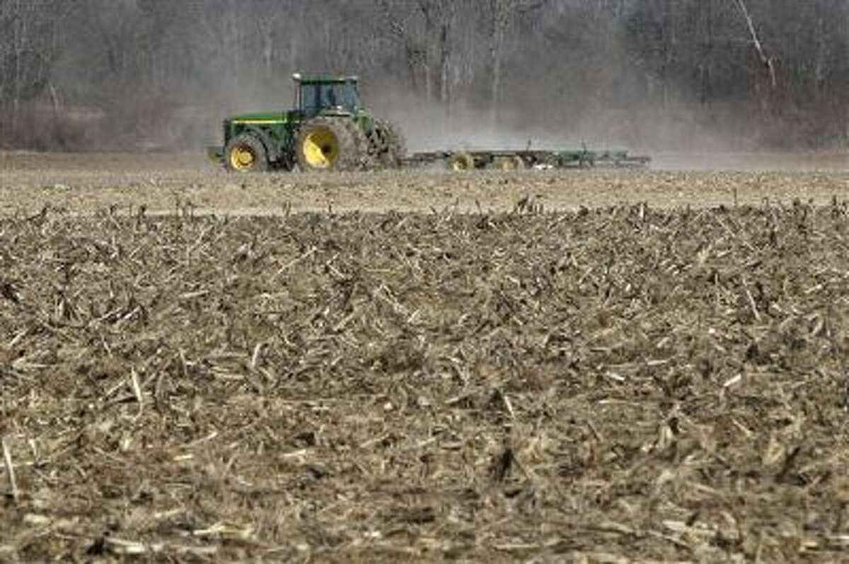 In this photo taken Thursday, Jan. 30, 2014, a farmer takes advantage of dry weather to till a field in preparation for spring planting near England, Ark. A new farm bill that could become law as soon as next week would require a choice between different subsidy approaches that require producers to suffer losses before they can get payouts. (AP Photo/Danny Johnston)