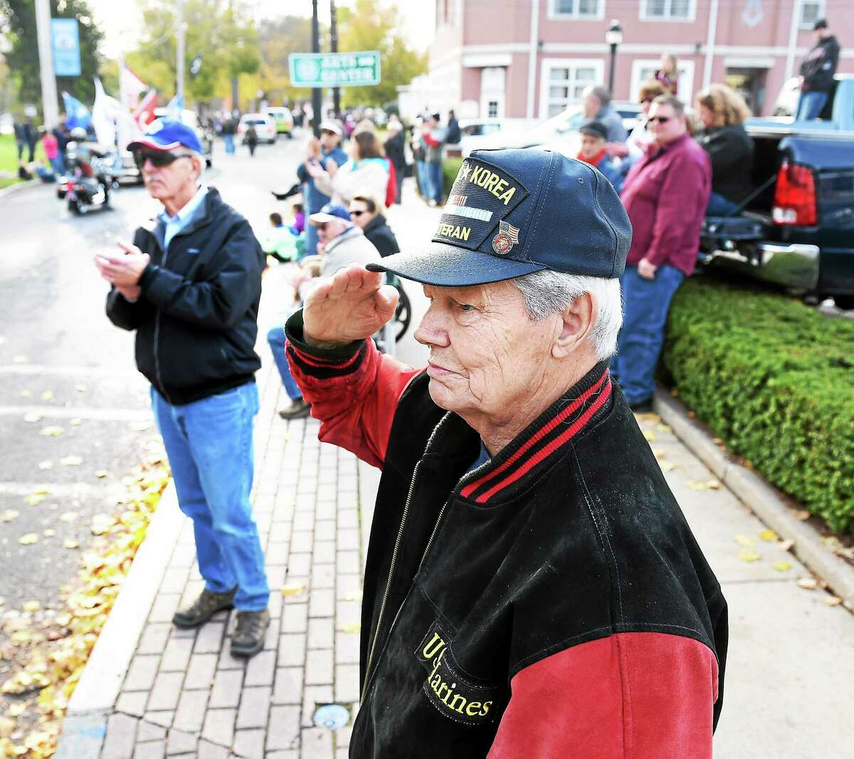 John D. Phillips, Sr., center, of Milford salutes the flag as it passes during a Veterans Day parade on Broad St. in Milford Sunday. Phillips served as a Marine in World War II and Korea.