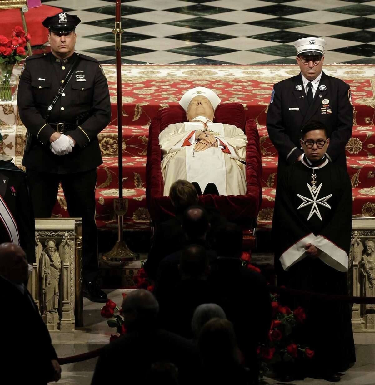 Officals stand around the body of Cardinal Edward Egan at a public viewing in St. Patrick's Cathedral in New York, Monday, March 9, 2015. Egan played a prominent role in New York City after the Sept. 11 terror attacks, and now New Yorkers are paying respects to the former archbishop after his death last week. (AP Photo/Seth Wenig)