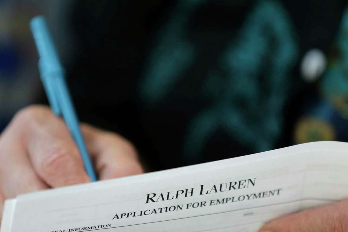 In this Tuesday, Oct. 6, 2015, photo, a job seeker fills out a job application during a job fair at Dolphin Mall in Miami. The Labor Department reports on the number of people who applied for unemployment benefits during the week ending Oct. 24 on Thursday, Oct. 29, 2015.