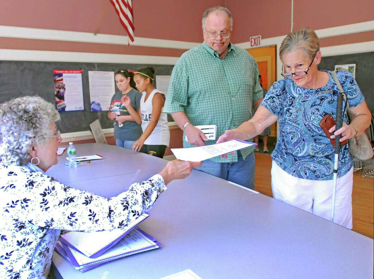 Middlefield residents Kathy and Gerald Begin pick up a ballot from Sharlene Menard to vote for the sale of Powder Ridge to Sean Hayes in this August 2012 file photo.