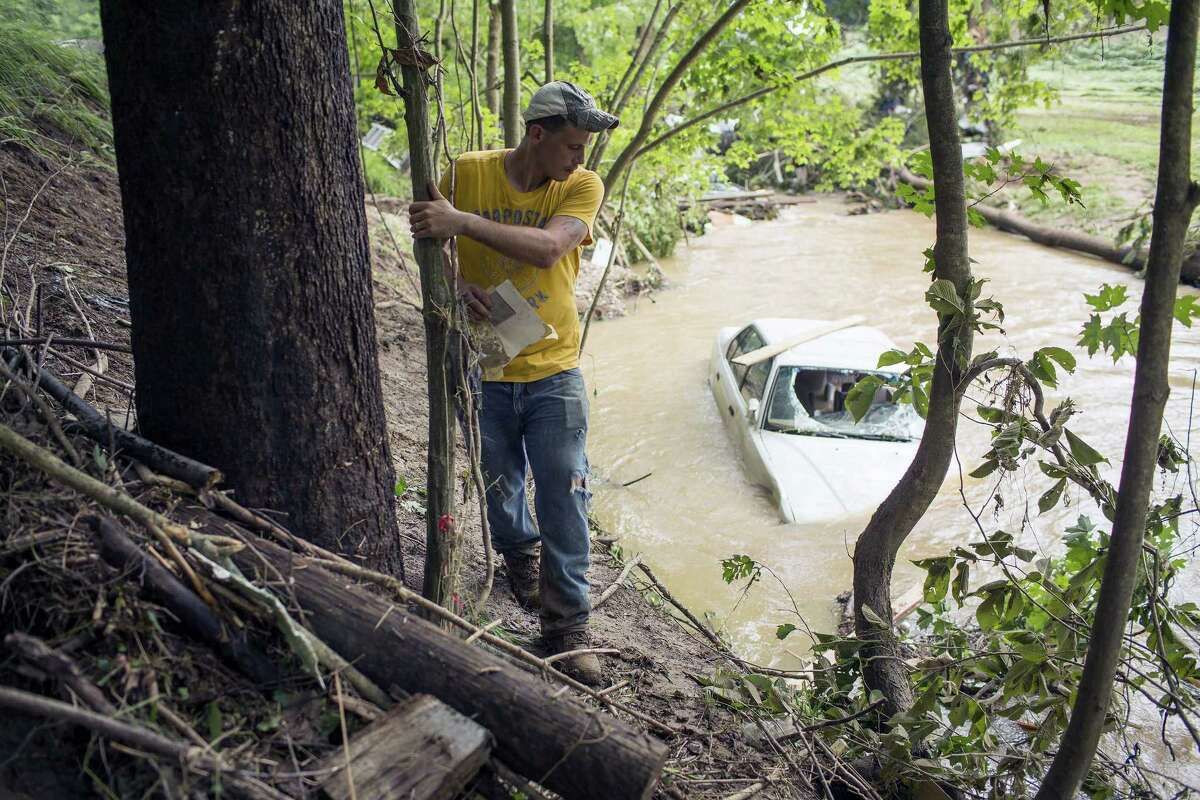 Ralph Whitaker checks a partially submerged vehicle while searching for his brother who was missing after deadly flooding in Flat Gap, Ky. on July 14, 2015. Flash floods in northern Johnson County outside of Paintsville destroyed homes and vehicles and residents were reported missing a day after the floods.