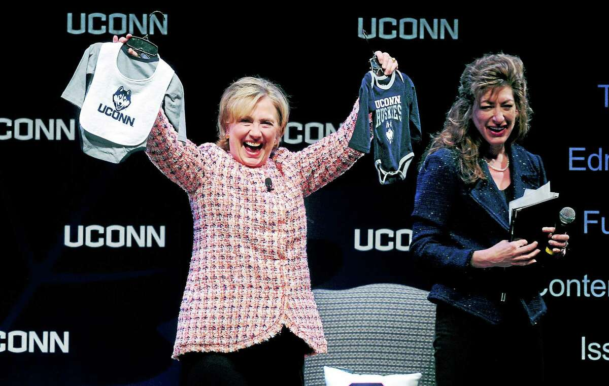 Former Secretary of State Hillary Clinton, left, shows off onesies given to her by University of Connecticut president Susan Herbst at the Edmund Fusco Contemporary Issues Forum at UConnon on April 23.