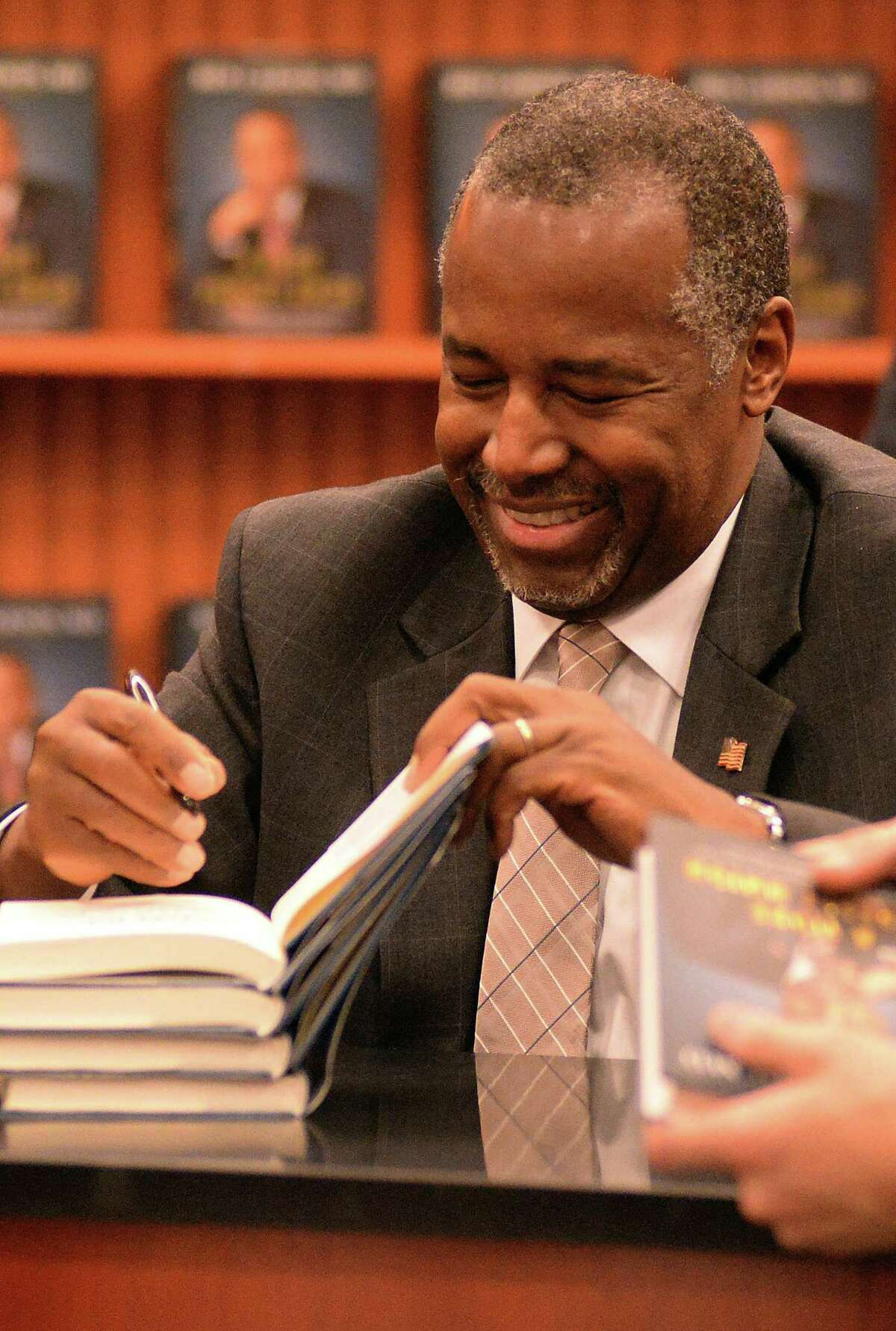 Presidential candidate Ben Carson, autographs his book during his book signing event in Lake Sumter Landing, The Villages, Fla., Monday, Nov. 2, 2015.