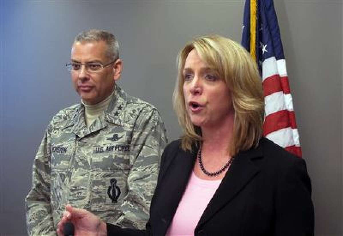 Maj. Gen. Jack Weinstein, left, listens as United States Secretary of the Air Force Deborah Lee James speaks Jan. 22 to members of the press during a trip to Minot Air Force Base in Minot, N.D. James said the visit was a fact-finding tour in response to cheating and drug scandals the Air Force recently revealed. (AP Photo/James MacPherson)