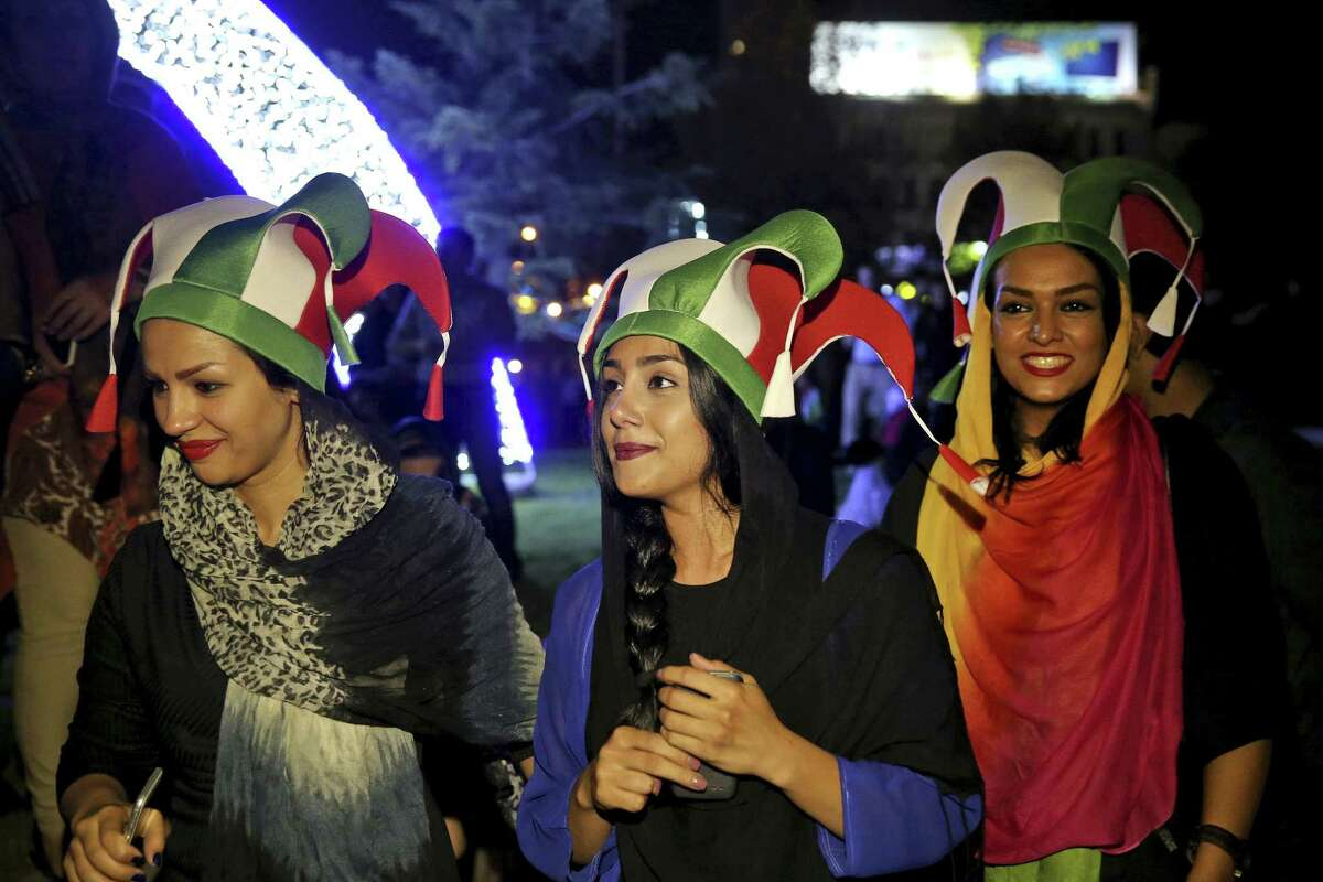 Iranian women take part in street celebrations following a landmark nuclear deal, in Tehran, Iran, Tuesday, July 14, 2015. Overcoming decades of hostility, Iran, the United States, and five other world powers struck a historic accord Tuesday to check Tehran's nuclear efforts short of building a bomb. The agreement could give Iran access to billions in frozen assets and oil revenue, stave off more U.S. military action in the Middle East and reshape the tumultuous region. (AP Photo/Ebrahim Noroozi)