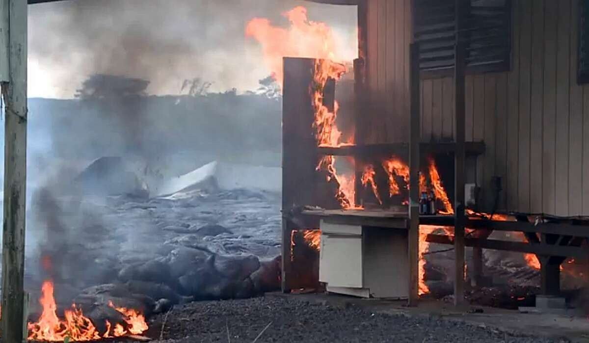 In this image made from video provided by the County of Hawaii, lava flow from the Kilauea Volcano burns a residential structure Monday, Nov. 10, 2014, in Pahoa, Hawaii. A stream of lava set a home on fire Monday in a rural Hawaii town that has been watching the slow-moving flow approach for months.