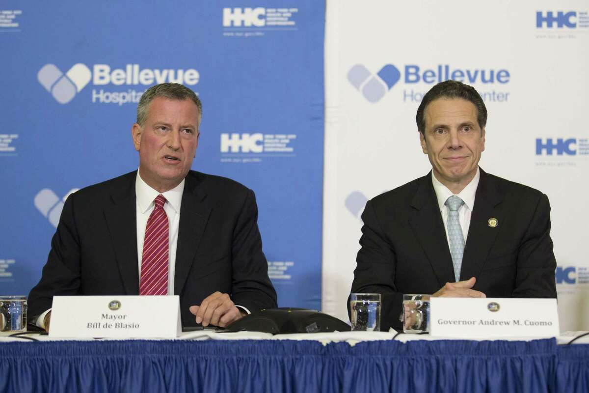 FILE- In this Oct. 23, 1024 file photo, New York City Mayor Bill de Blasio, left, joins New York Gov. Andrew Coumo at a news conference at Bellevue Hospital after New York City physician Dr. Craig Spencer had tested positive for the Ebola virus after returning from West Africa where he treated Ebola patients.
