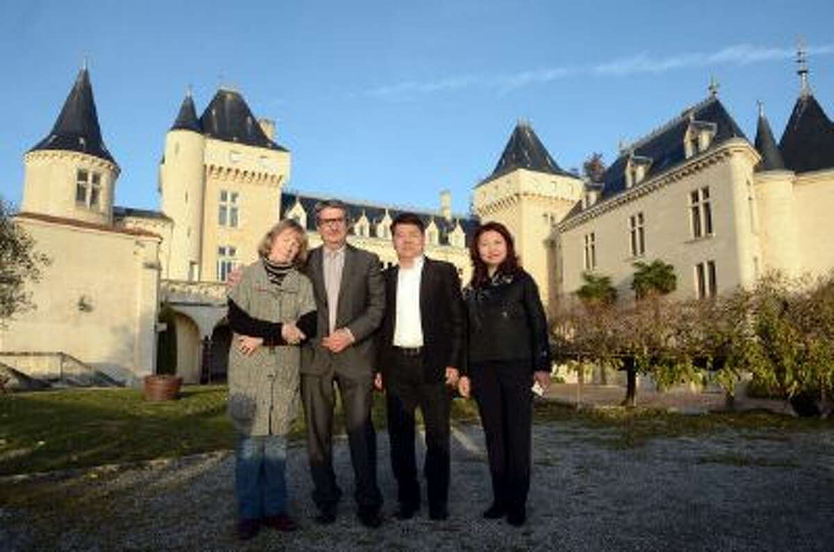 Chinese billionaire Lam Kok and his spouse pose alongside the French former owner of the Chateau de La Riviere, James Gregoire, and his spouse in front of the castle in La Riviere, on Dec. 20, 2013, shortly after Kok agreed to purchase the property. Both Kok and Gregoire were killed in a helicopter crash while surveying the property shortly after this photo was taken.