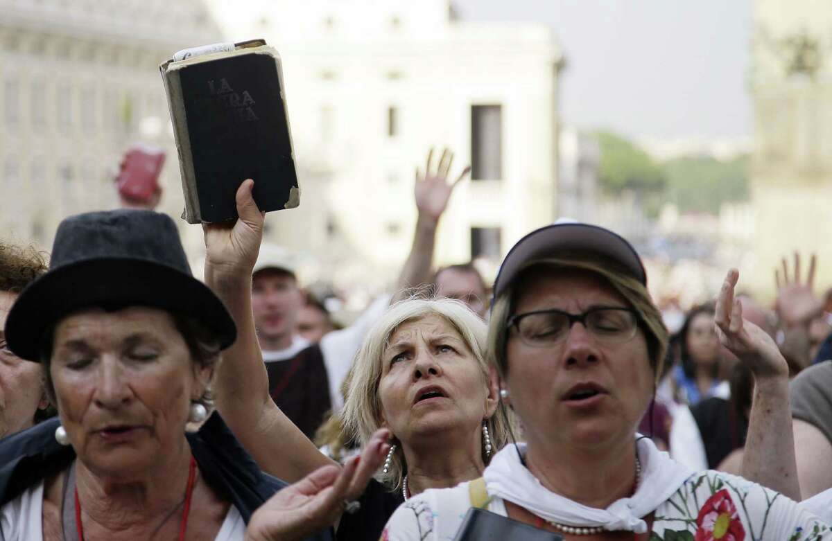 A woman holds up the Holy Bible as people crowd St. Peter's Square on the occasion of Pope Francis' meeting with faithful of the Holy Spirit movement at the Vatican, Friday, July 3, 2015. (AP Photo/Gregorio Borgia)