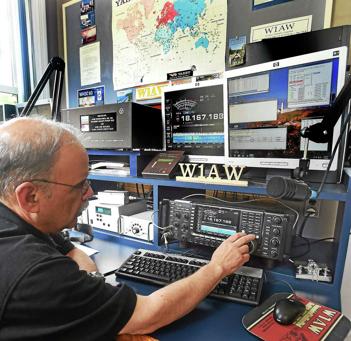 American Radio Relay League COO Harold Kramer tunes in a radio in one of the modern booths at W1AW in Newington.