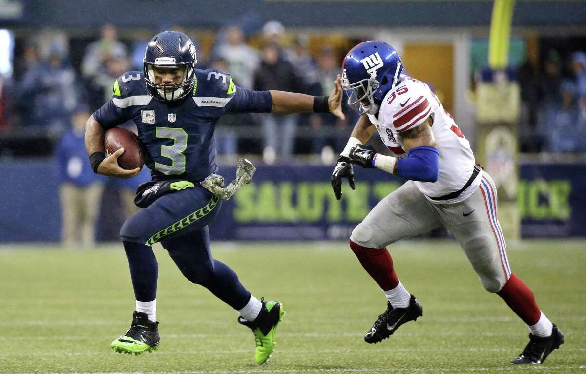 Seattle Seahawks quarterback Russell Wilson (3) gets ready to push off of New York Giants' Quintin Demps during the second half of an NFL football game, Sunday, Nov. 9, 2014, in Seattle. The Seahawks won 38-17. (AP Photo/Elaine Thompson)