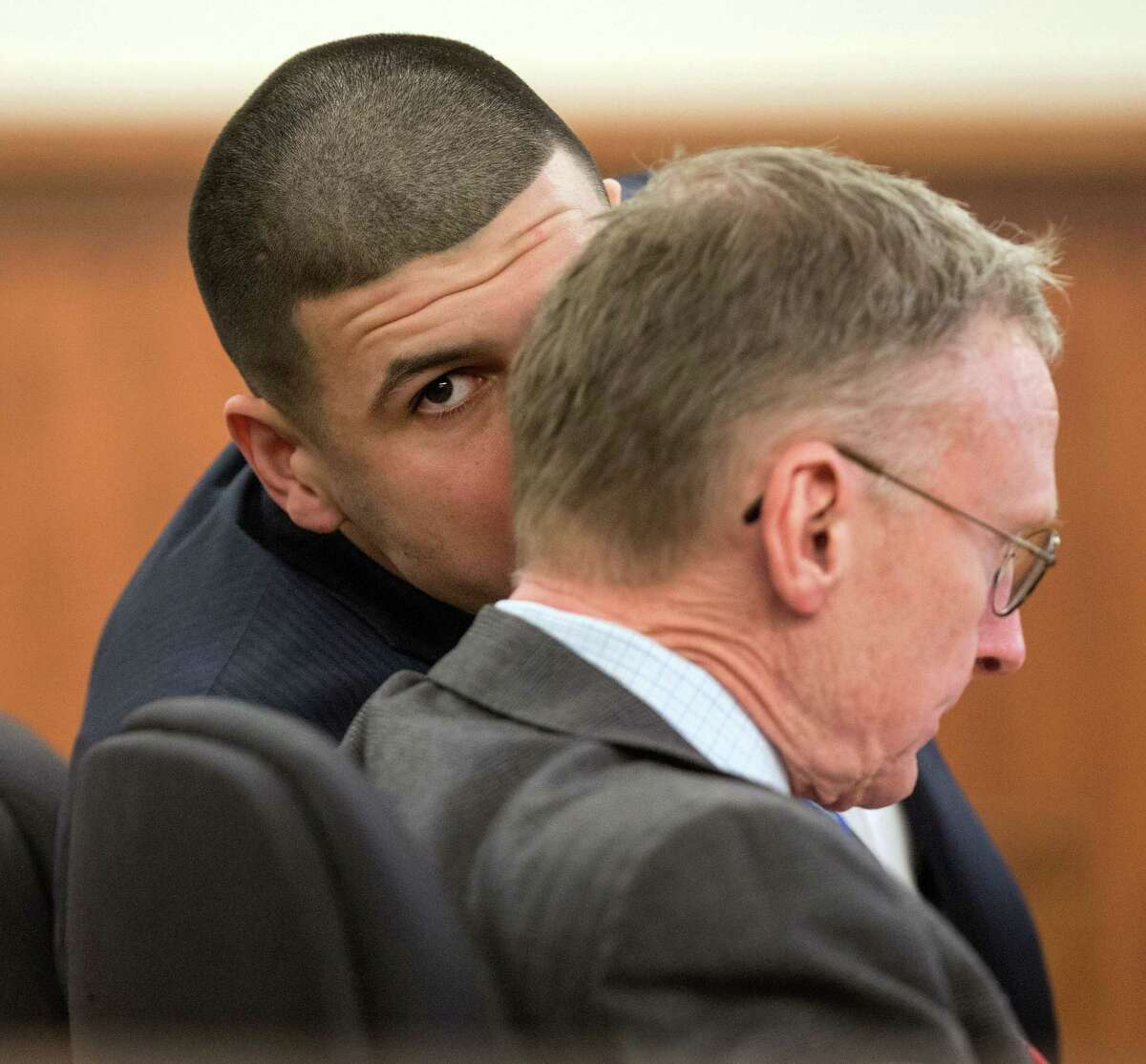 Former New England Patriot Aaron Hernandez, left, speaks with his attorney Charles Rankin during his trial Monday at Bristol County Superior Court in Fall River, Mass.