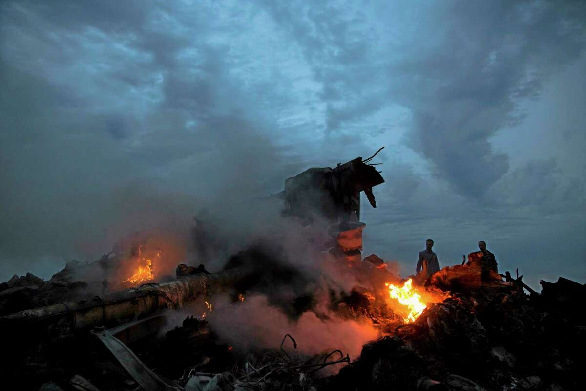 People walk amongst the debris at the crash site of a passenger plane near the village of Hrabove, Ukraine, Thursday, July 17, 2014. Ukraine said a passenger plane was shot down Thursday as it flew over the countr. Both the government and the pro-Russia separatists fighting in the region denied any responsibility for downing the plane. (AP Photo/Dmitry Lovetsky)