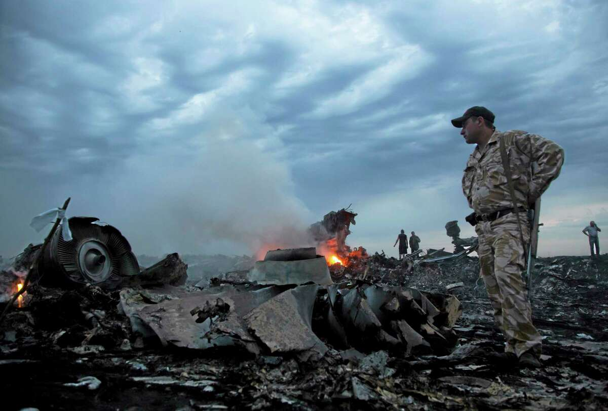 People walk amongst the debris, at the crash site of a passenger plane near the village of Grabovo, Ukraine, Thursday, July 17, 2014.