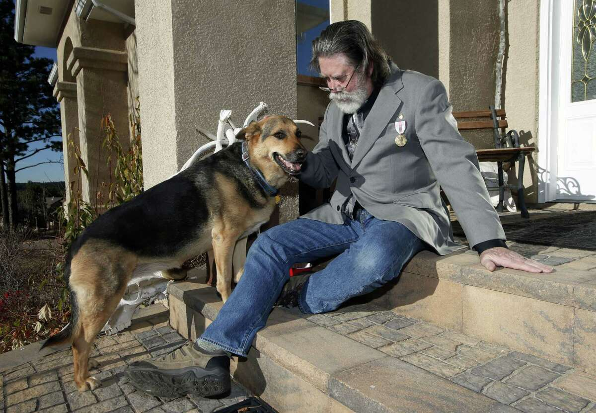 AP Photo/David Zalubowski Robert Curtis poses with his dog, Jasmine, a German Shepherd/Iraeli Canaan mix, at his home, on Thursday, Nov. 6, 2014. A $10 billion-a-year effort to protect sensitive government data, from military secrets to Social Security numbers, is struggling to keep pace with an increasing number of cyberattacks and is unwittingly being undermined by federal employees and contractors. Curtis, according to court records, was besieged by identity thieves after someone stole data tapes that a federal contractor left in a car, exposing the health records of about 5 million current and former Pentagon employees and their families.